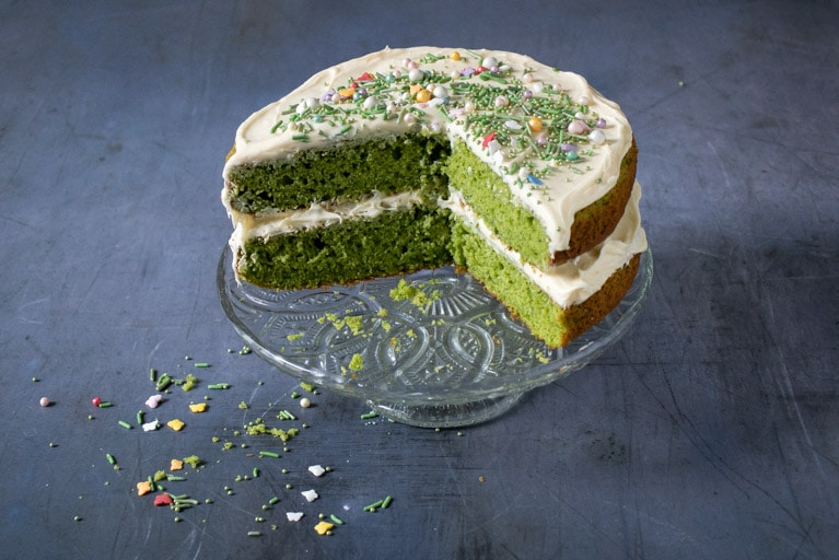 A Vanilla Spinach layer cake with vanilla frosting covered in pretty sprinkles on a vintage cake stand. A slice has been taken out to reveal the bright green colour of the cake, even though the spinach flavour can't be tasted and it just tastes like a vanilla cake.