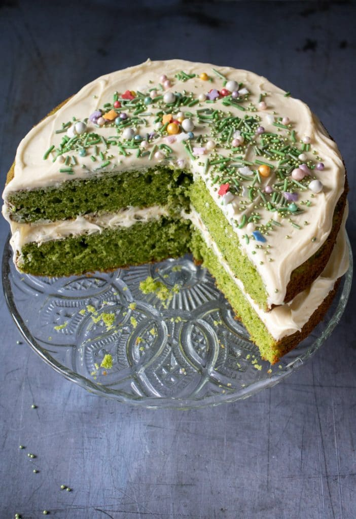 Overhead shot of a bright green layer cake. This vanilla spinach cake with vanilla frosting and sprinkles is a bright green cake, but the flavour of the spinach fades away so it just tastes of vanilla.