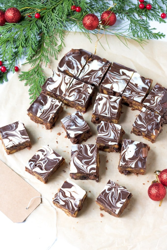 Slices of Christmas Chocolate Tiffin - a perfect edible gift. Shown with milk and white chocolate swirled on top next to gift tags, baubles and Christmas tree branches.