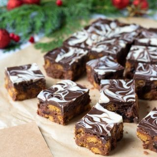 Close up of squares of gingerbread and spiced Christmas Tiffin - layers of cookies and dried fruit with chocolate, then a milk and white chocolate swirled topping. Shown next to gift tags as it's a great edible gift.