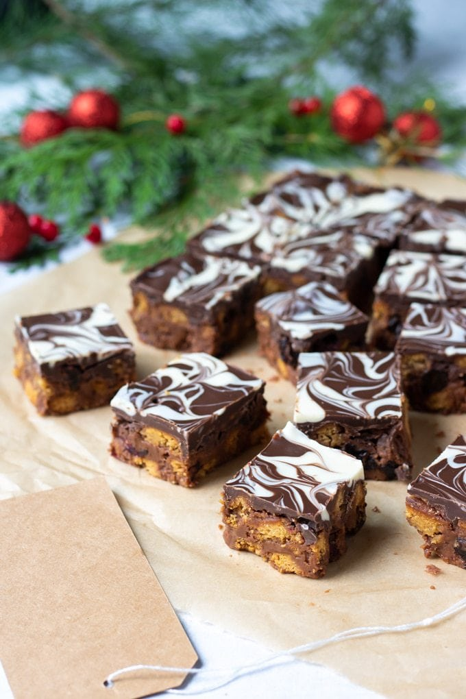 Squares of chocolate tiffin in front of xmas ornaments and pine boughs.