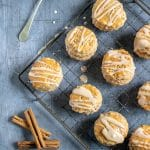 A vintage rack with cinnamon scones with vanilla cinnamon drizzle, next to a spoon and cinnamon sticks. Get the recipe.
