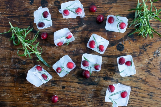 Cranberry and rosemary ice cubes on a wooden table