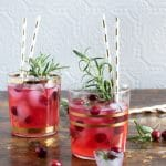 Glasses of ginger cranberry kombucha cocktail recipe with gold paper straws and sprigs of rosemary