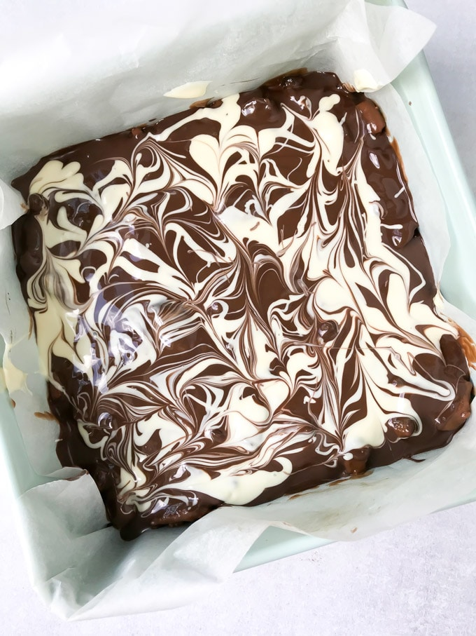 How to make Christmas Chocolate Tiffin. Step 7: Melt the dark and white chocolate separately. Pour the melted dark chocolate over the tiffin, then drizzle the white chocolate over it and use a cocktail stick or knife to create swirls. Chill in the fridge for 1 hour to set, then cut into small bars.