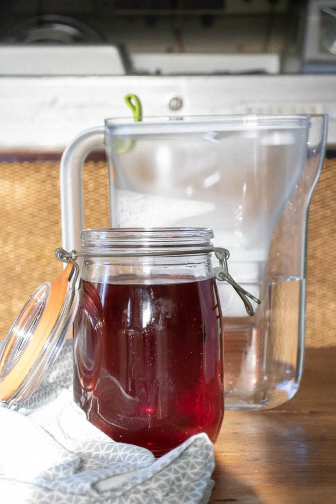 How to make kombucha - step 2 - after the tea has cooled a bit, top up with more filtered water and pour into a jar