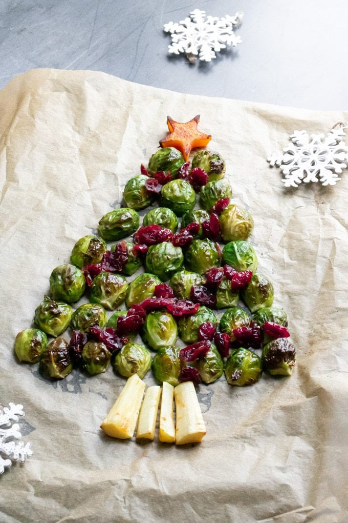 Roasted sprouts in the shape of a Christmas tree. Dried cranberries are on top as decorations with roasted parsnips as the tree trunk and butternut squash for the star at the top.
