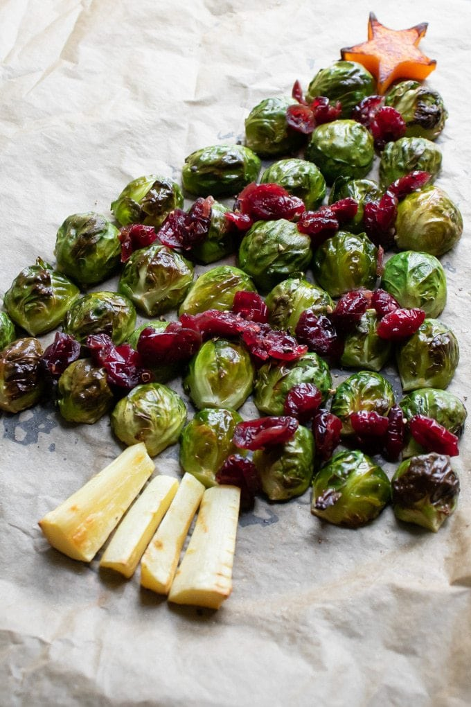 Close view of roasted brussles sprouts in the shape of a Christmas tree, with cranberry decorations, parsnip tree trunk and butternut squash star cut with a cookie cutter.