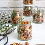 Small jars of Rosemary Maple Spiced Roasted Nuts with sprigs of rosemary, next to vintage scissors