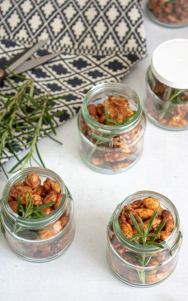 Rosemary Maple Spiced Roasted Nuts - small jars filled with nuts and a sprig of rosemary, perfect for an edible gift. On a white background next to a blue and white patterned tea towel. Get the recipe.