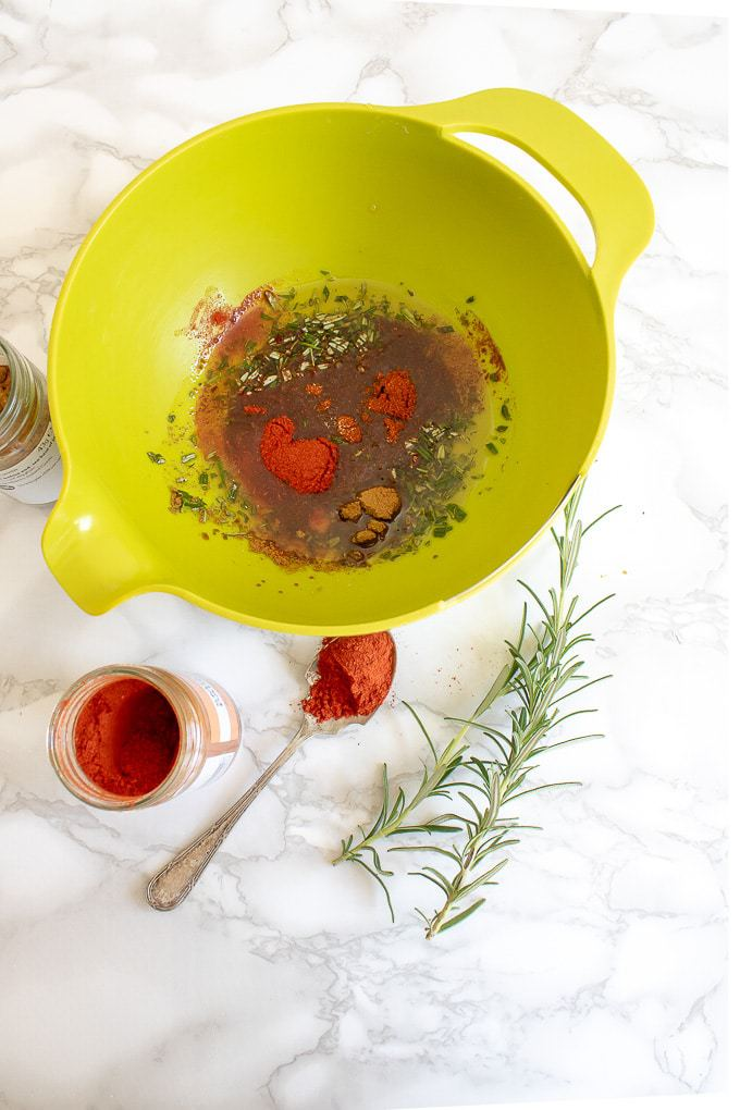 How to make Rosemary Maple Spiced Roasted Nuts - mix the melted coconut oil and maple syrup with the herbs and spices in a bowl