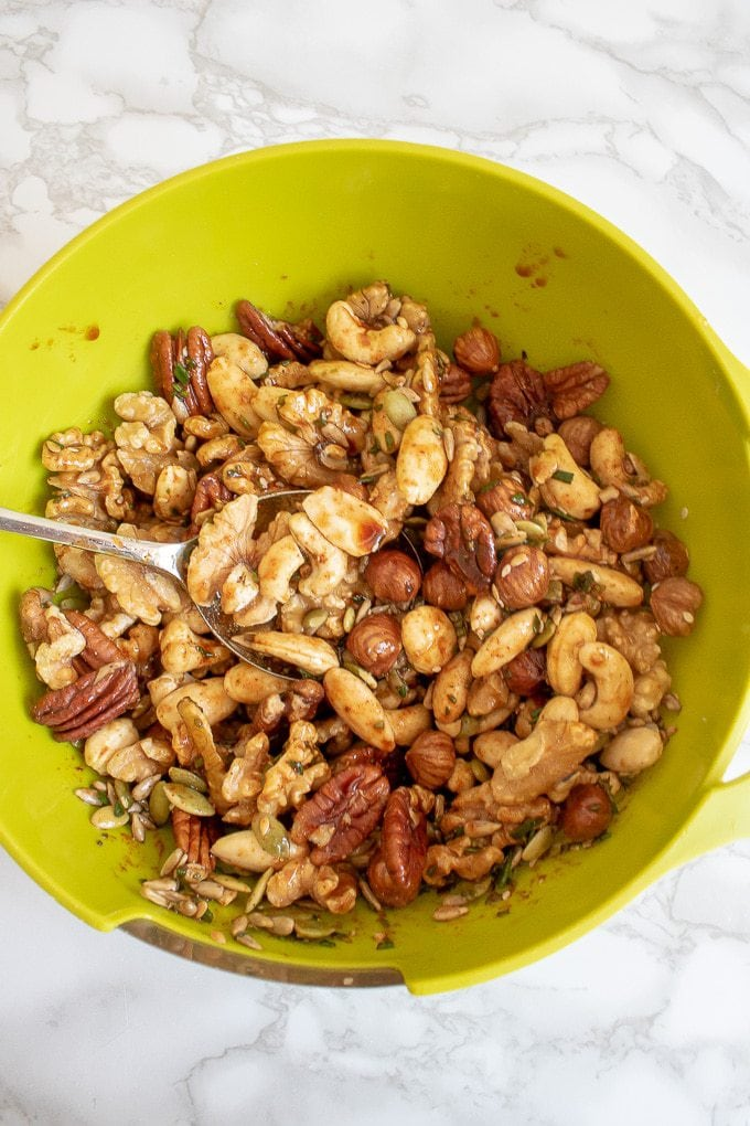 How to make Rosemary Maple Spiced Roasted Nuts - add the mixed nuts and stir well to coat completely.