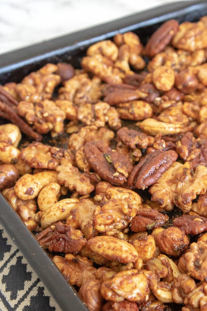 How to make Rosemary Maple Spiced Roasted Nuts - add to a baking sheet and roast until slightly darker