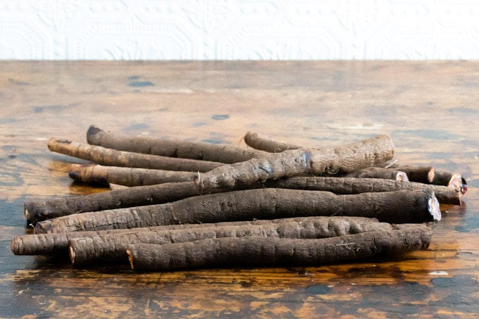 A pile of Salsify - a root vegetable - on a wooden table with a white textured wall in the background