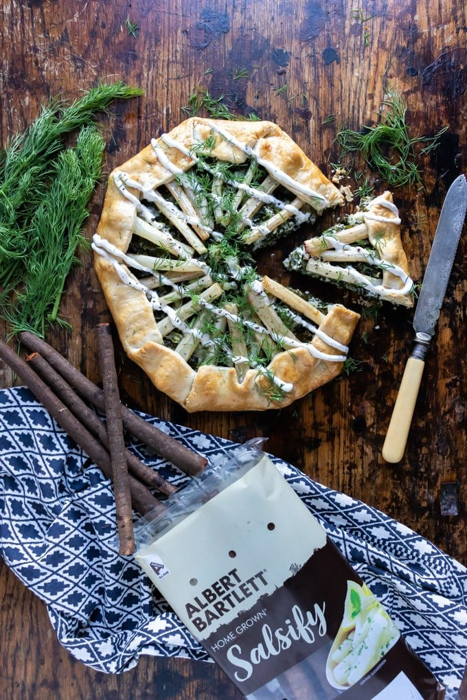 Overhead shot of salsify kale galette - a free form pastry filled with a thick layer of creamed kale and topped with sticks of salsify (a root vegetable popular in continental Europe), with horseradish sauce drizzled over the top and sprinkled with dill. Get the recipe.