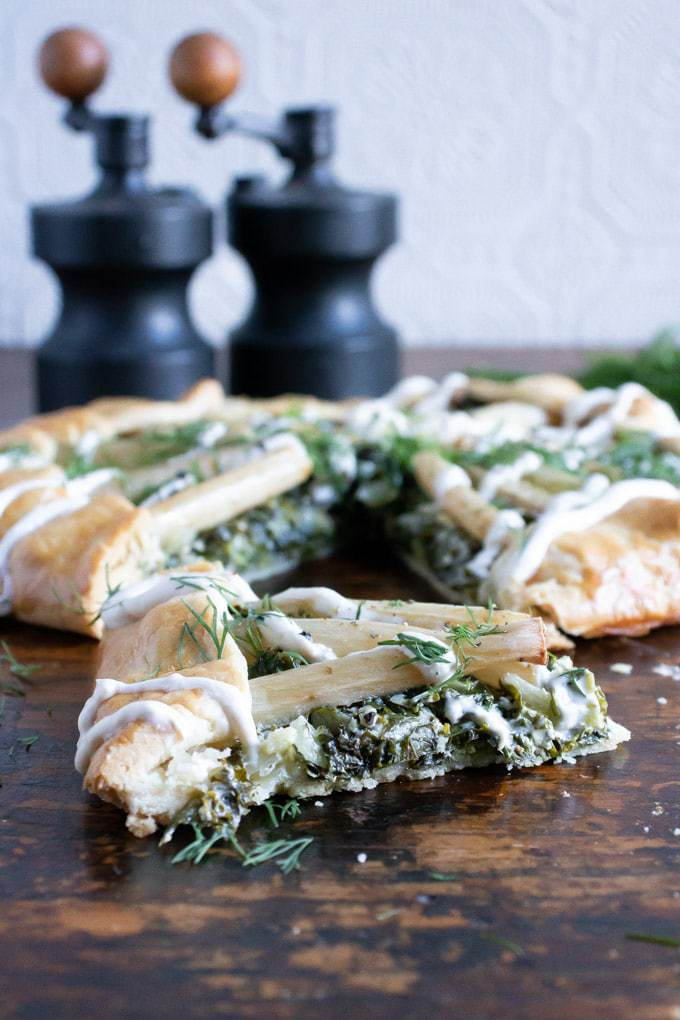 Close up side view of a slice of salsify kale galette with vintage salt and pepper shakers in the background. This salsify recipe uses the root vegetable on top of a bed of creamed kale, wrapped in a free form pastry galette. It's then drizzle in horseradish cream and sprinkled with dill.