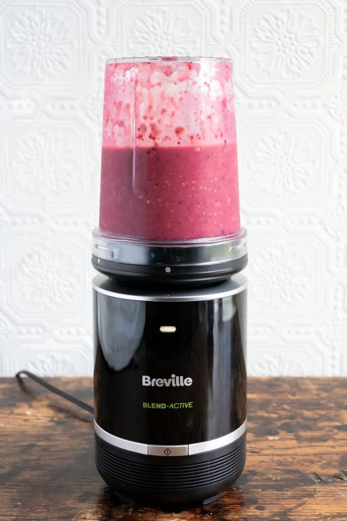Breville Blend Active Pro Food Prep Blender Set with acai smoothie being blended in it.