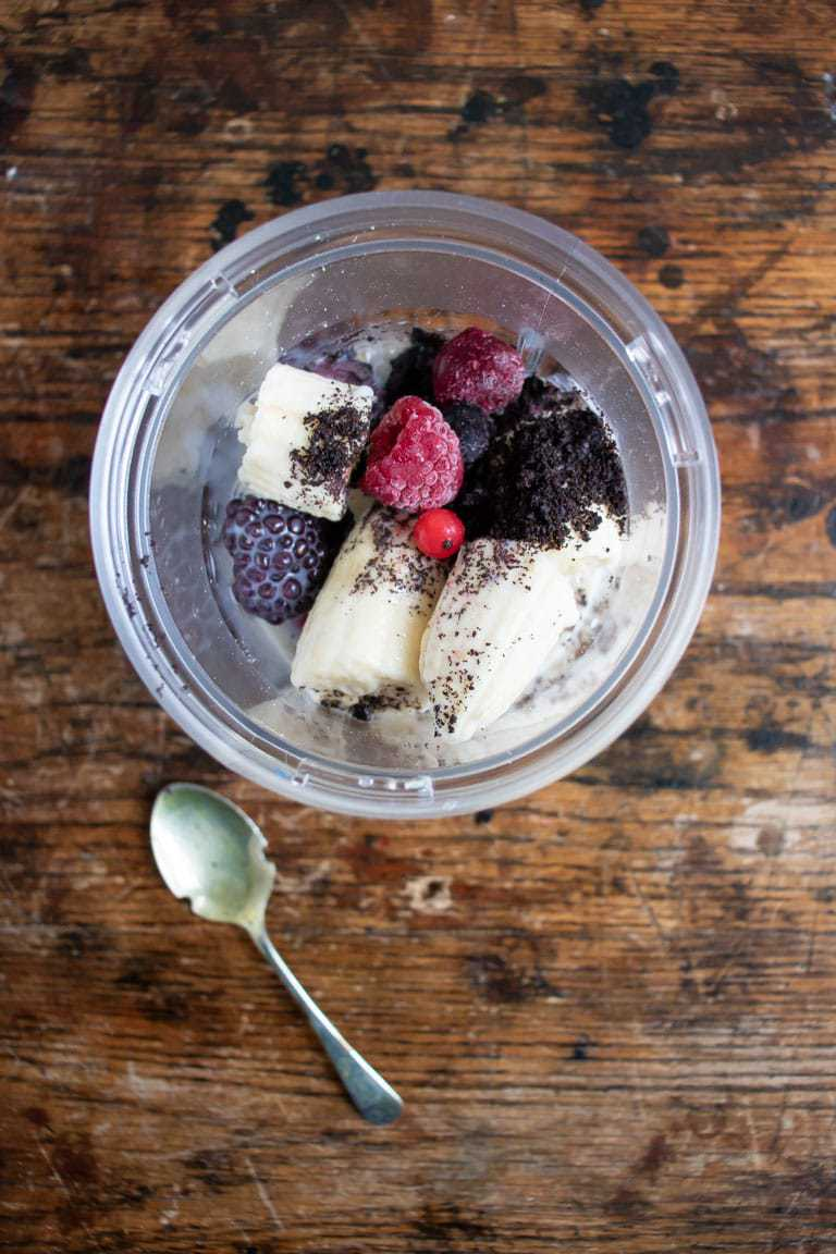 Ingredients for acai smoothie bowl in a blender - banana, plant milk, acai powder, frozen berries, oats, vanilla, maple syrup.