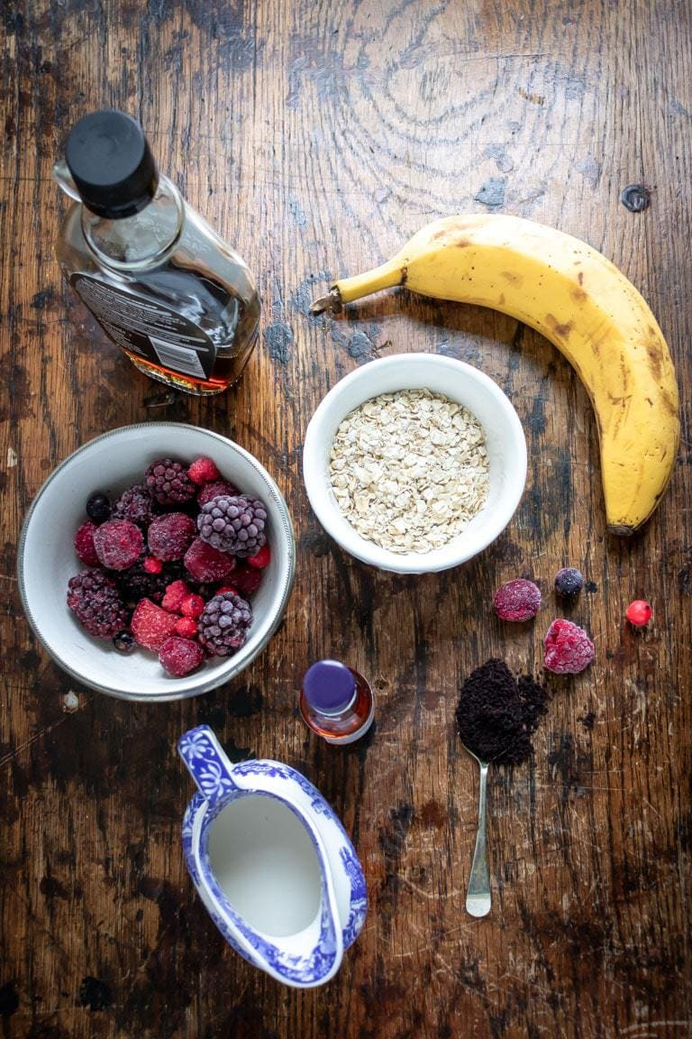 Ingredients for acai smoothie bowl recipe on a wooden table - banana, oats, acai powder, plant milk, vanilla, maple syrup, frozen berries.