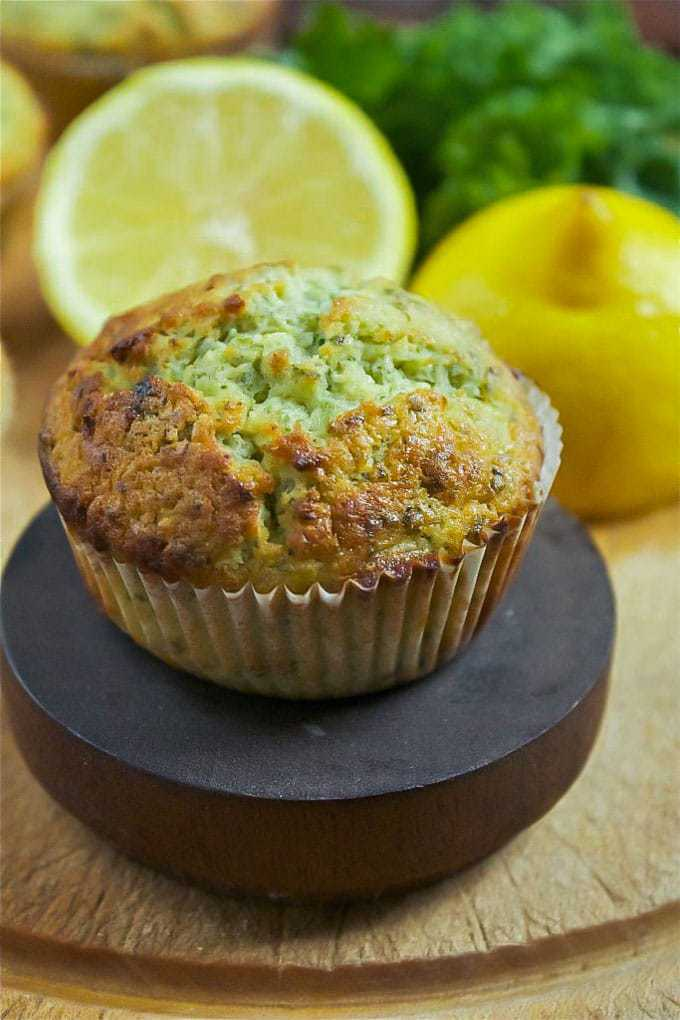 A tasty lemon and kale muffin close up with lemon and kale in the background.