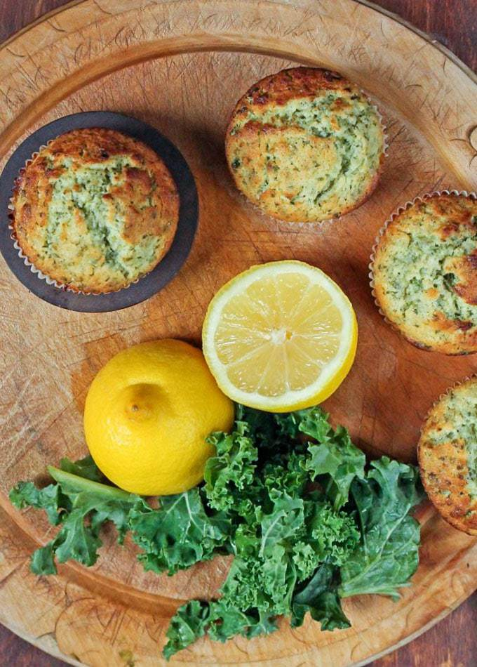A wooden board with green lemon kale muffins next to cut lemons and fresh kale.