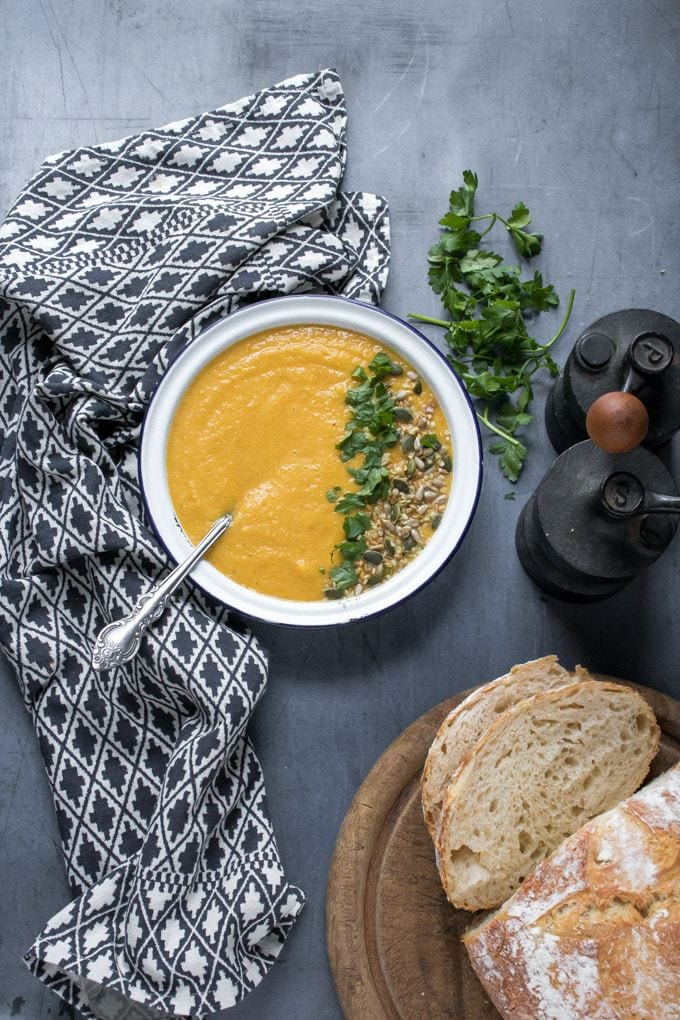 A blue background and patterned tea towel, with a white bowl filled with velvety smooth creamy vegan lentil soup. Topped with fresh herbs and seeds. This easy 7 ingredient recipe is shown next to vintage pepper mill and sliced fresh bread.