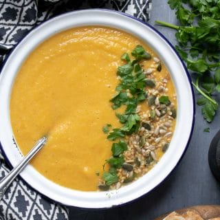 A bowl of creamy vegan lentil soup, topped with fresh herbs and seeds. On a blue background with fresh herbs scattered around.