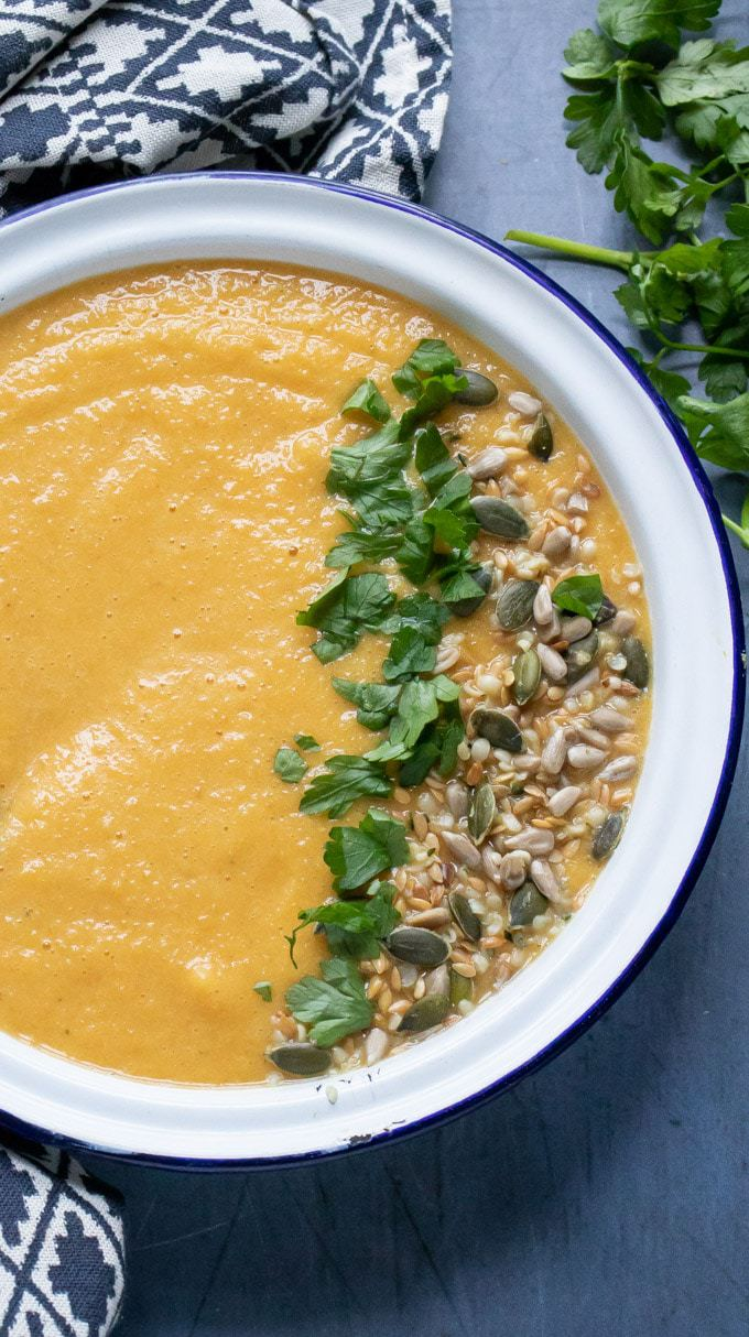 A creamy smooth vegan lentil soup recipe in a white bowl sprinkled with fresh herbs and seeds. An easy 7 ingredient recipe.