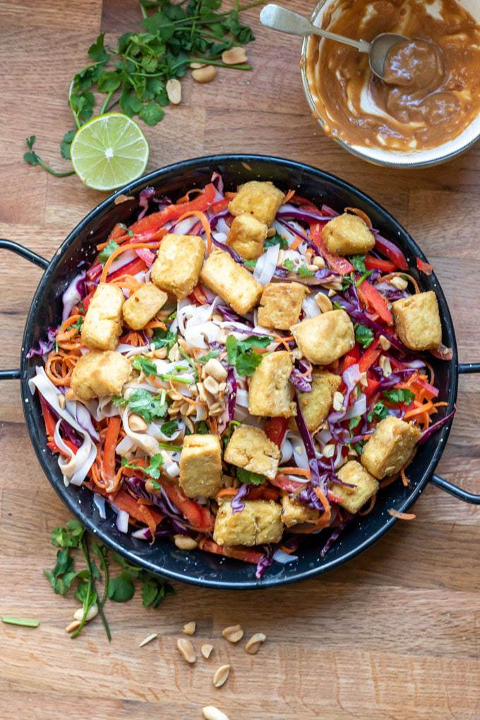 Overhead shot of a noodle bowl with rice noodles, thinly sliced veggies and airfryer tofu. Shown next to a lime, fresh herbs, peanuts and a bowl of easy peanut sauce. Get the vegan and gluten free recipe.