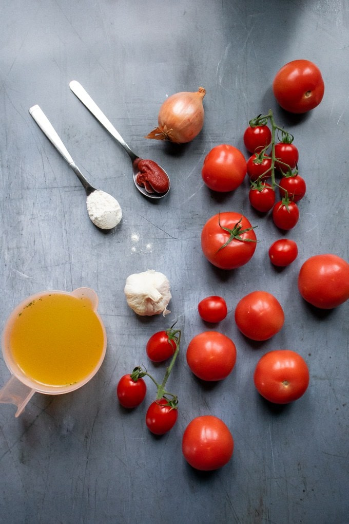 Ingredients for easy fresh tomato soup recipe - a blue background with fresh tomatoes, stock/broth, garlic, onion, tomato paste