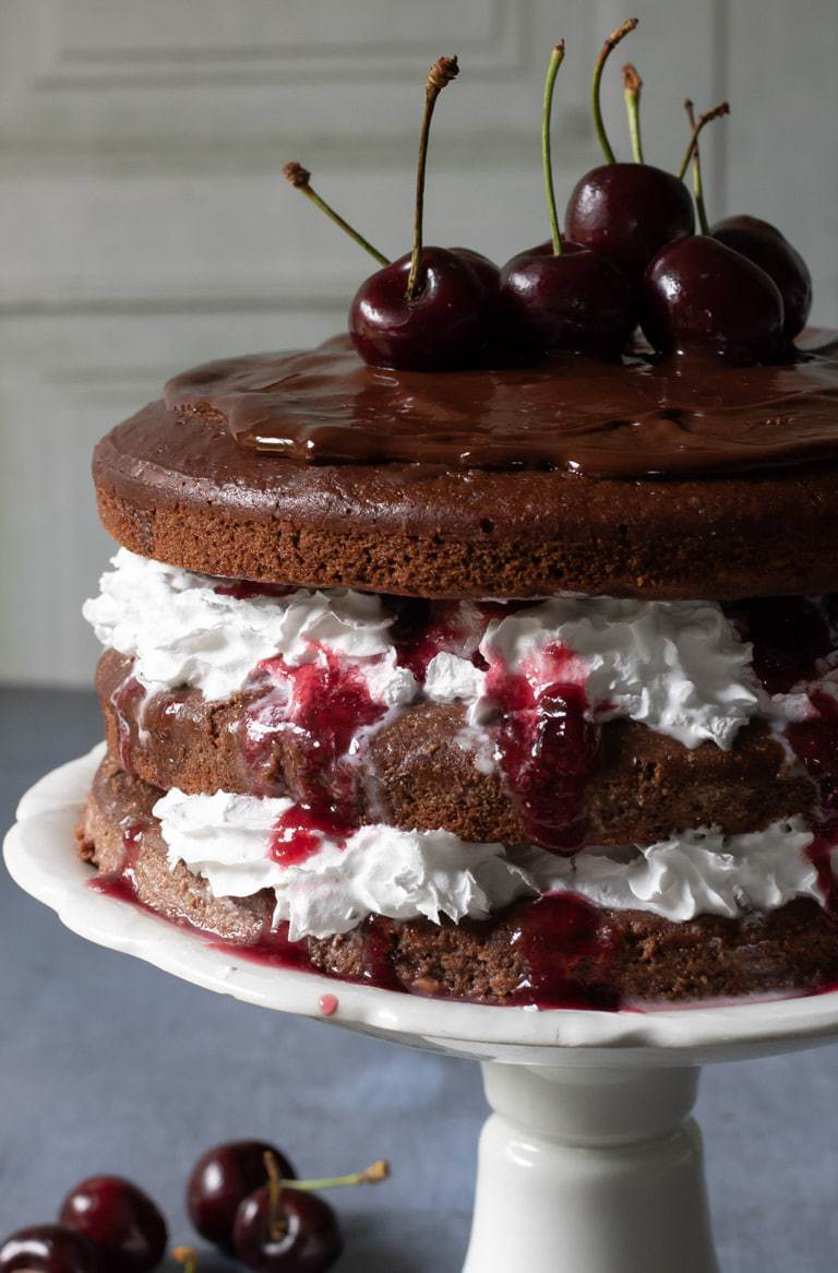 Close up of a rich delicious Vegan Black Forest Cake - with three layers of decadent chocolate cake, with thick cream and cherry sauce between the layers. The top is spread with a chocolate ganache and fresh cherries adorn the top. Get the vegan cake recipe now.