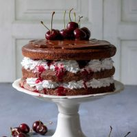 A rich delicious Vegan Black Forest Cake - with three layers of decadent chocolate cake, with thick cream and cherry sauce between the layers. The top is spread with a chocolate ganache and fresh cherries adorn the top. Shown in front of a white panelled wall on a blue table top on white vintage cake stand with cherries scattered around. Get the vegan dessert recipe now.