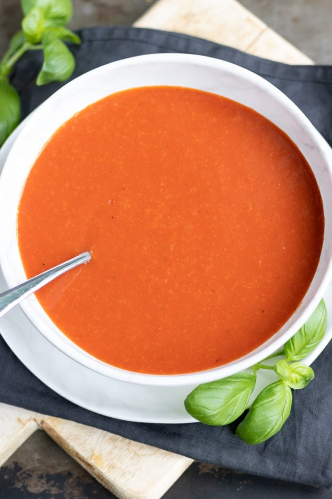 Close up of a bowl of homemade tomato soup using canned or fresh tomatoes. Next to fresh basil leaves.