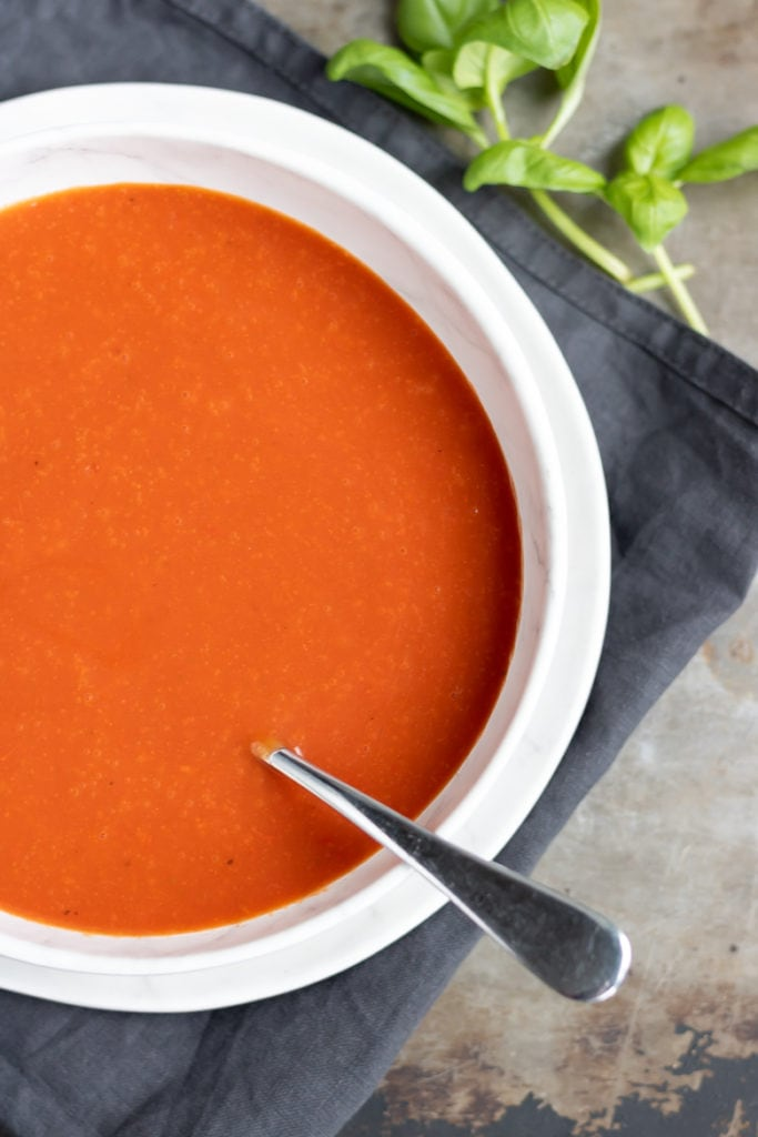 Bowl of homemade creamy tomato soup from scratch on a dark napkin