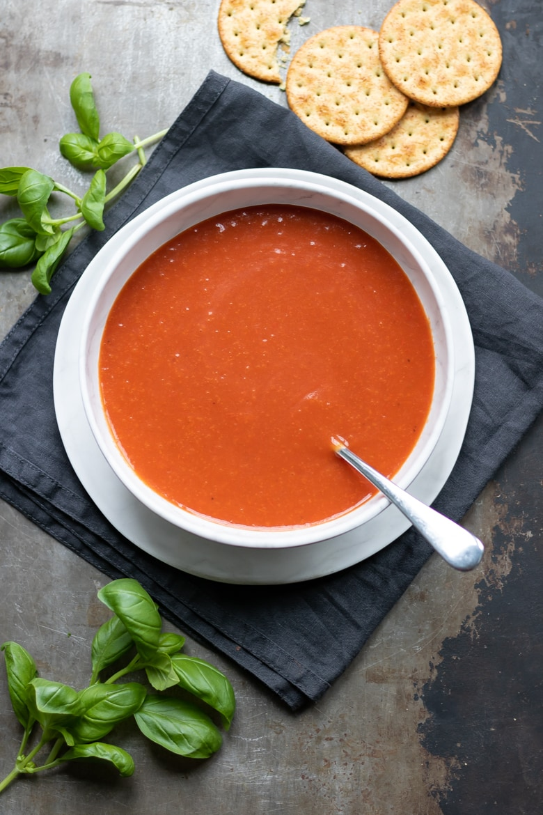 A bowl of cream of tomato soup recipe topped with fresh herbs and seeds. Shown next to a blue and white tea towel with fresh vine tomatoes, vintage pepper mill and slices of fresh bread. Get the easy 20 minute tomato soup recipe now.