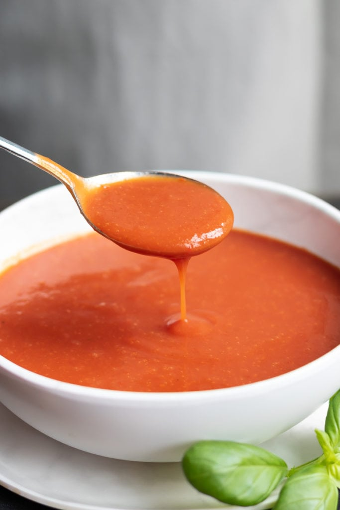 Spoon dripping into a bowl of easy homemade tomato soup recipe.