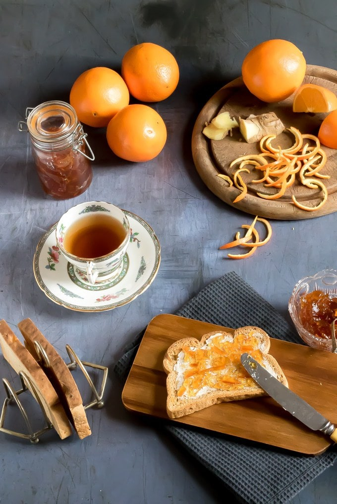 Easy ginger and orange marmalade recipe. Shown being spread on toast next to a cup of tea