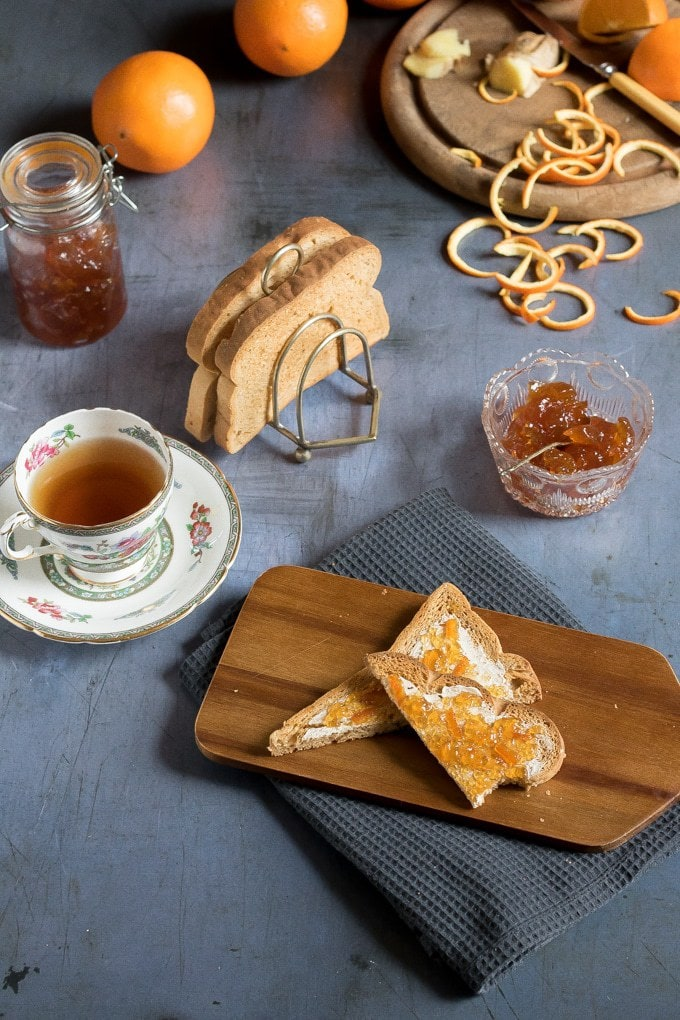 A bowl and jar of ginger orange marmalade (an easy recipe) next to marmalade on toast and teacups.