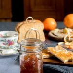 A jar of homemade ginger orange marmalade preserves recipe, in front of toast and teacups.