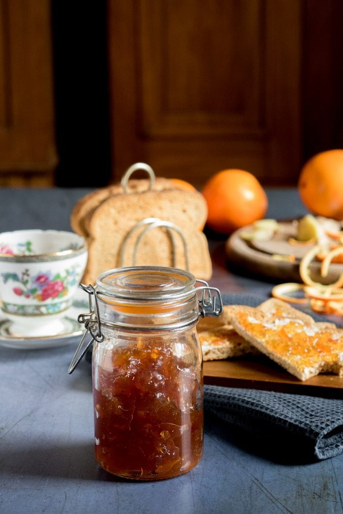 A jar of homemade ginger orange marmalade preserves recipe, in front of toast and teacups