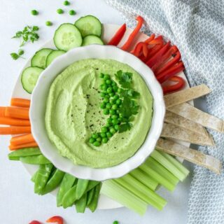 A bowl of fluffy pea hummus surrounded by raw vegetables and topped with peas and herbs. This recipe is so easy and makes a beautiful green dip.