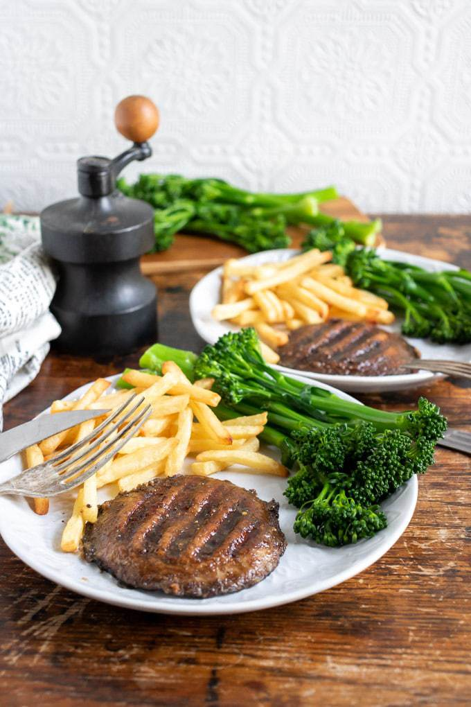 Two plates with marinated grilled mushroom steaks, served with broccolini and fries. Table set for two with this vegan recipe.