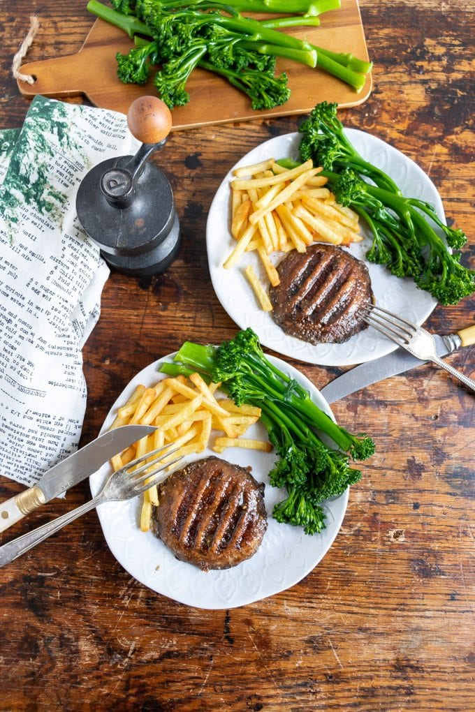 Overhead photo of two plates with vegan marinated grilled portobello mushroom steaks served with broccoli and fries. Vegan version of steak and chips recipe.