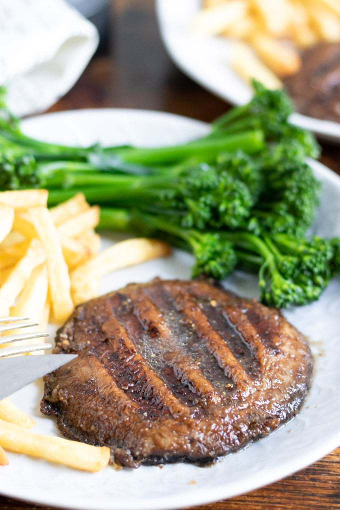 Close up of a mushroom steak on a plate with broccoli and fries.
