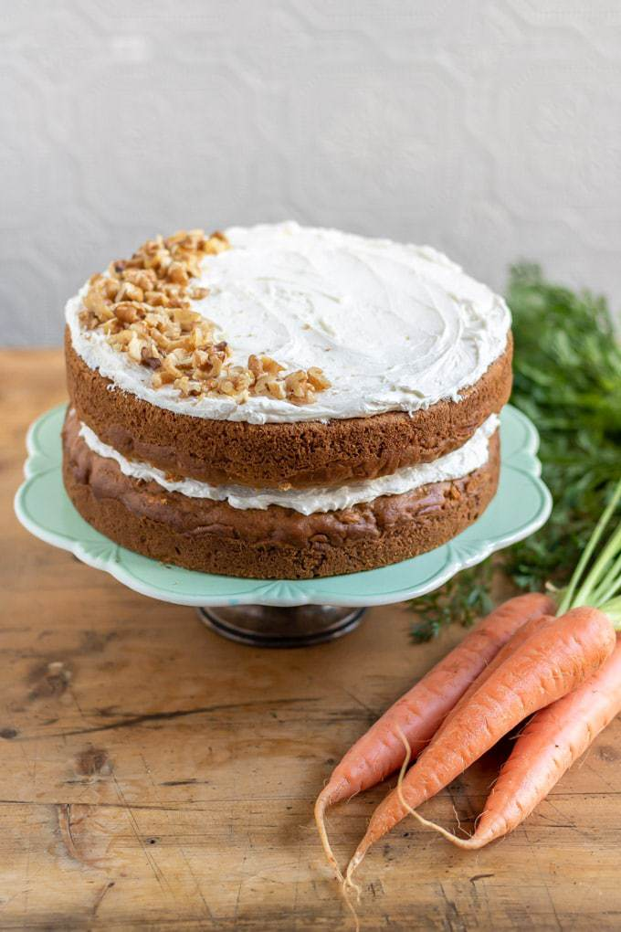 A vegan carrot cake with vegan cream cheese frosting. This easy one bowl layer cake is shown on a cake stand with walnuts sprinkled on the top.