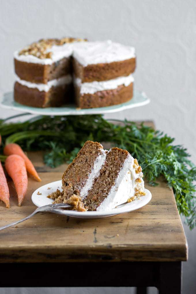 A two layer easy moist vegan carrot cake recipe with vegan cream cheese frosting. This super moist and delicious one bowl vegan cake is shown with a slice in the front of a carrot cake on a cake stand.