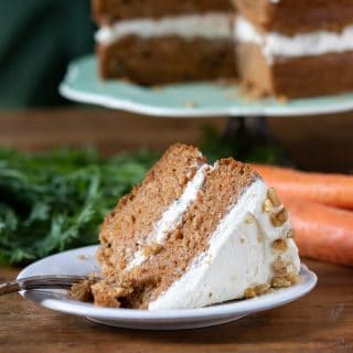 A slice of two layer vegan carrot cake. It's moist, fluffy and delicious one bowl easy recipe. Shown with vegan cream cheese frosting and walnuts.