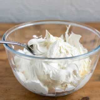 A bowl filled with thick and fluffy vegan cream cheese frosting recipe. In a glass bowl on a wooden table.