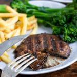 Close up of a marinated grilled portobello mushroom steak shown with mushroom jus on a plate with broccoli and fries. An easy vegan dinner for two recipe.