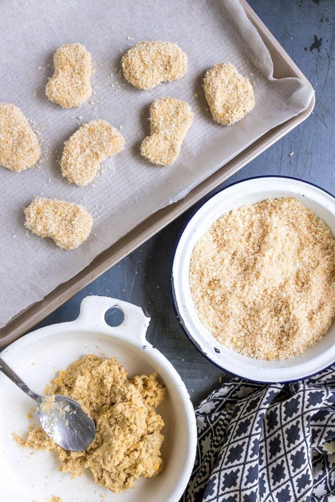 How to make vegan chicken nuggets recipe (chickpea nuggets). Breadcrumbs in a bowl, filling in a bowl and some vegan chicken nuggets on a baking tray.